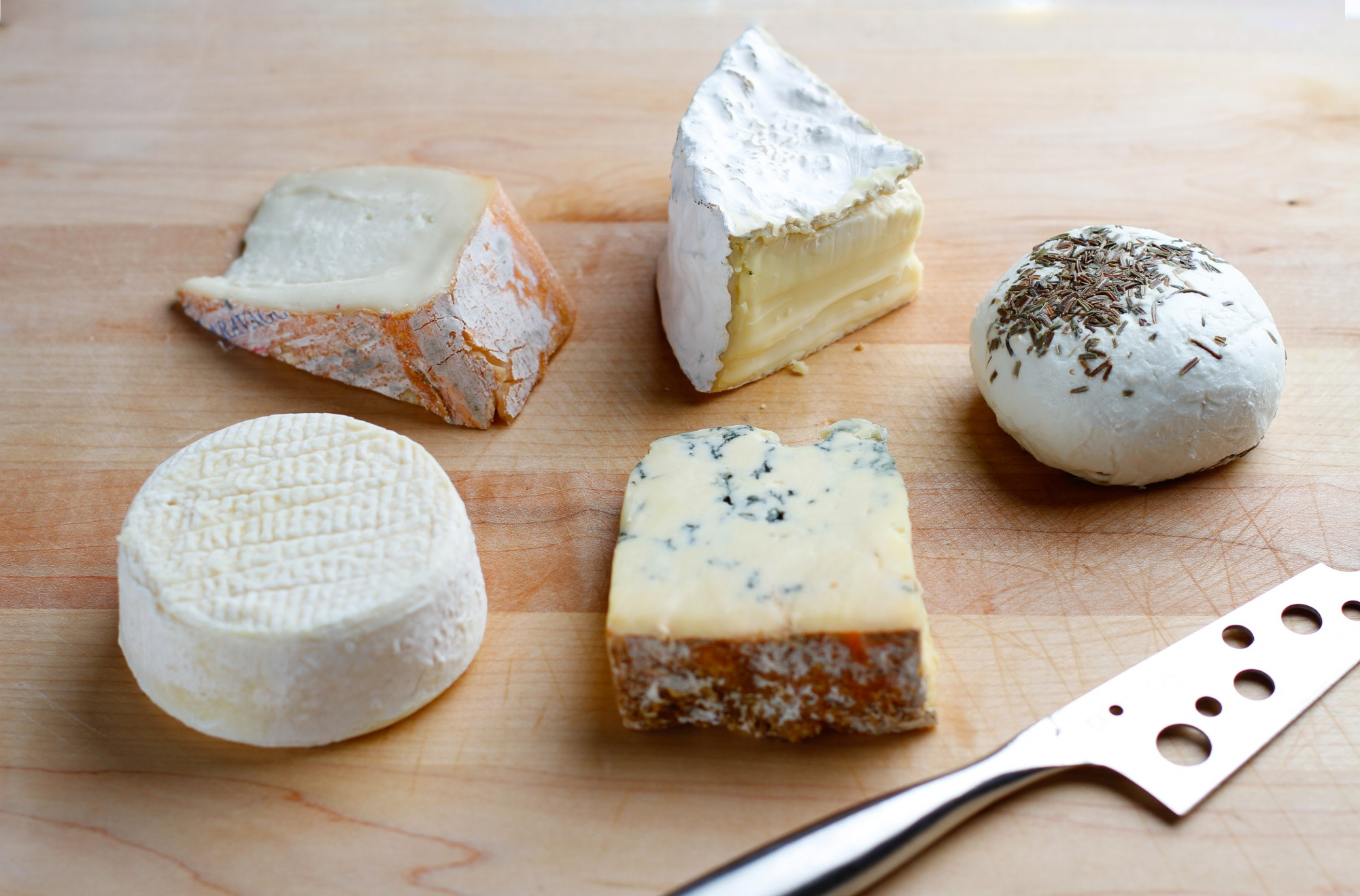 cheeses on wood with knife